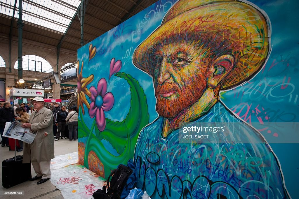 Passengers stand next to a mural in tribute to Dutch painter Vincent Van Gogh by French artist Nowart (Arnaud Rabier) at the Gare du Nord train station in Paris on September 22, 2015.