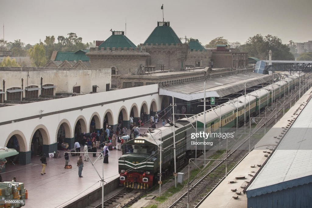 Passengers stand on a platform as a Green Line Express train operated by Pakistan Railways between Islamabad and Karachi sits at Rawalpindi railway...
