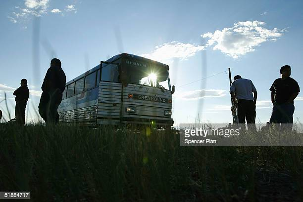 Passengers stand on the roadside during a short Greyhound bus layover in Wyoming August 13 2004 Greyhound the iconic bus company will stop servicing...