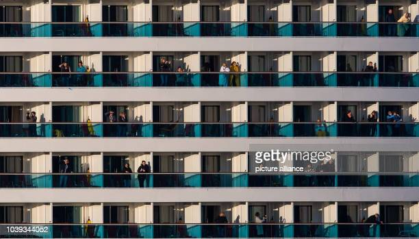 Passengers stand on their balconies as the new flagship 'Aidaprima' of shipping company Aida Cruises arrives at the port of Hamburg Germany 21 April...