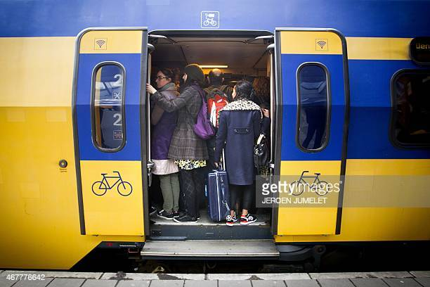 Passengers stand onboard a crowded train at the Central Station in Utrecht The Netherlands on March 27 as public transport services were effected due...