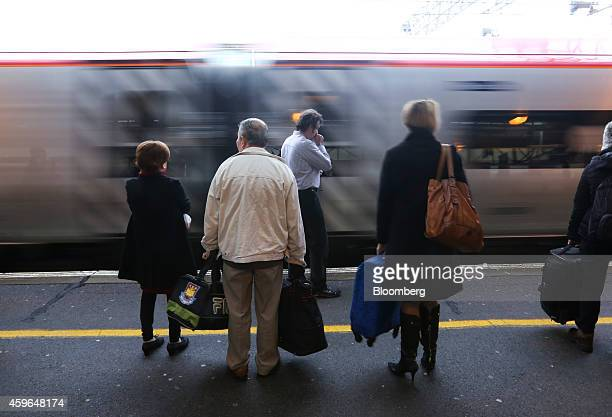 Passengers stand with luggage as a West Coast train operated by Virgin Trains arrives beside a platform at Milton Keynes railway station in Milton...