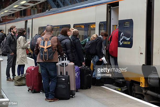 Passengers stand with their luggage as they wait to board a Eurostar train operated by Eurostar International Ltd ahead of departure from St Pancras...