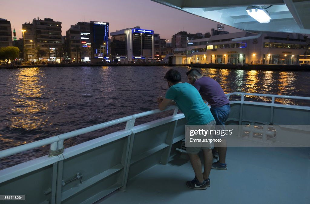 Passengers standing and chatting at the deck of passenger ferry at sunset in Izmir. : Stock Photo