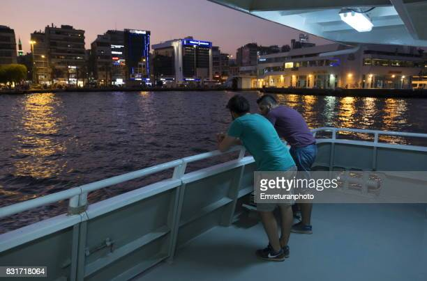 passengers standing and chatting at the deck of passenger ferry at sunset in izmir. - emreturanphoto stock pictures, royalty-free photos & images
