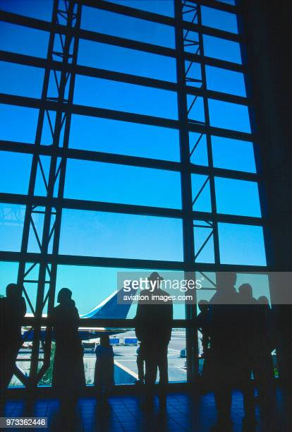 passengers standing by the window of the departurelounge of the Tom Bradley Terminal with the tailfin of a Boeing 757200 parked outside behind