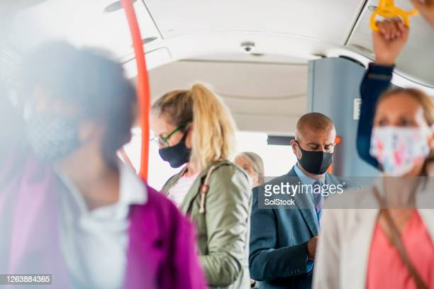 passengers staying protected during rush hour - public transport stock pictures, royalty-free photos & images