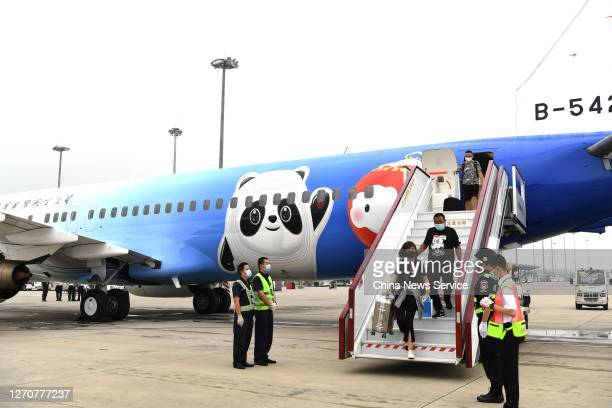 Passengers step off a newly painted Boeing 737 aircraft of Air China with patterns of the emblems and mascots of Beijing 2022 Winter Olympics at...