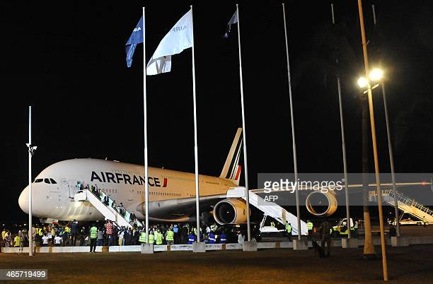^Passengers step out of an Airbus A380 of French airline Air France upon their arrival at Abidjan's airport on January 28 2014 It is the first A380...