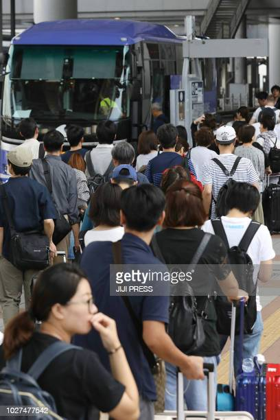 Passengers stranded at the Kansai International Airport due to typhoon Jebi board a bus to be transported from the airport in Izumisano city Osaka...