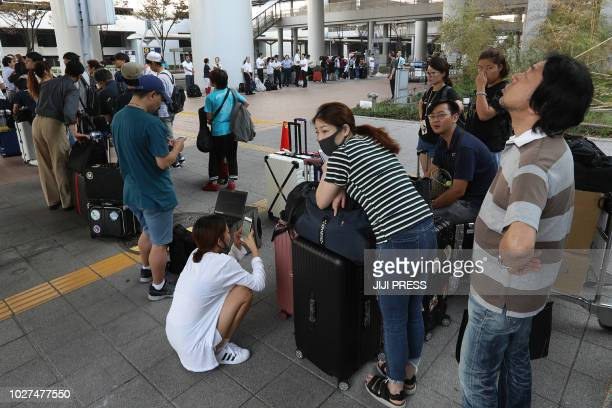 Passengers stranded at the Kansai International Airport due to typhoon Jebi wait for buses that will transport them from the airport in Izumisano...
