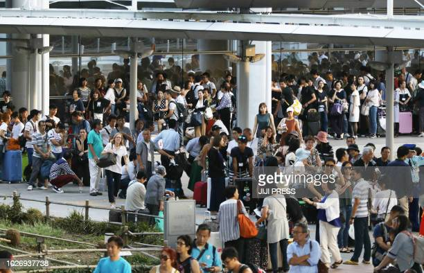 Passengers stranded overnight at the Kansai International Airport due to typhoon Jebi wait for buses that will transport them from the airport in...