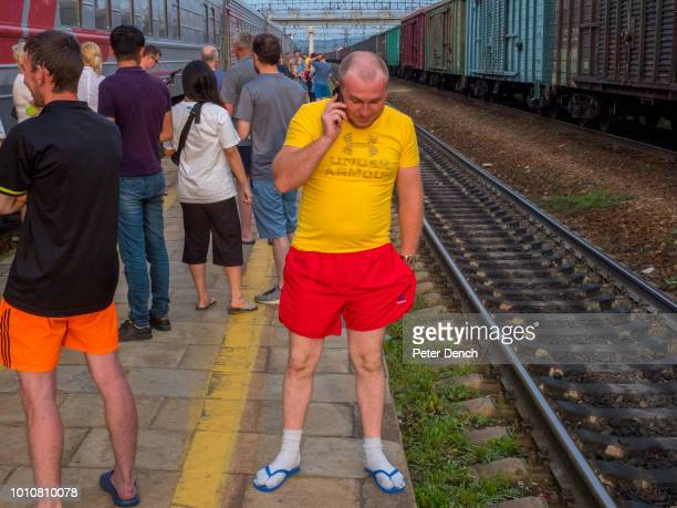 Passengers stretch their legs during a scheduled stop on the TransSiberian Railway from MoscowVladivostok spanning a length of 9289km it's the...