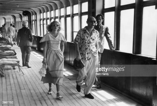 Passengers strolling on the promenade deck of the Cunard liner Queen Elizabeth as she makes her way to Britain across the Atlantic America wants to...