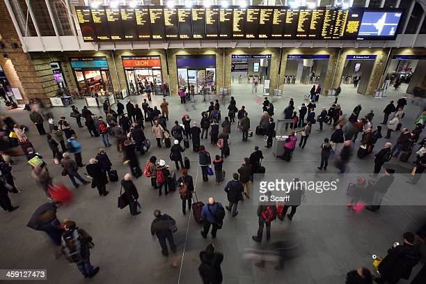Passengers study the departure boards as they wait for trains in Kings Cross Station on December 23 2013 in London England With two days until...