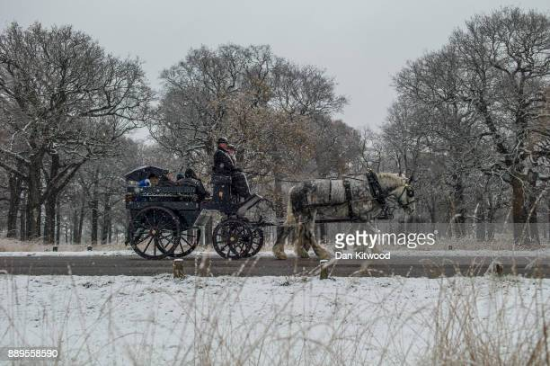Passengers take a horse and carriage ride through heavy snow in Richmond Park on December 10 2017 in London England