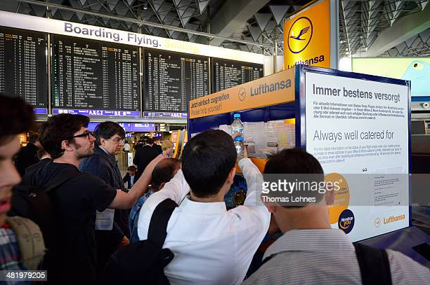 passengers take drinks and snacks in front of the destination board with the canceled Lufthansa flights at Frankfurt Airport on April 2 2014 in...