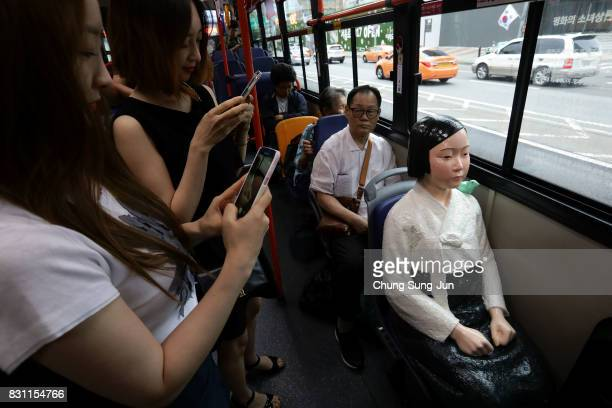 Passengers take photos a comfort woman statue installed in a bus ahead of the 72nd Independence Day on August 14 2017 in Seoul South Korea The statue...