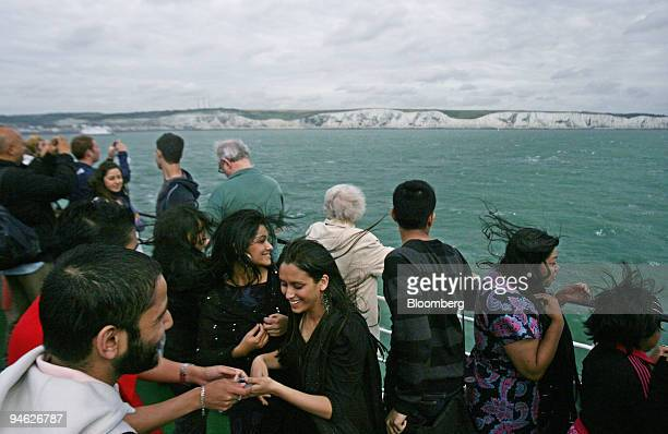 Passengers take photos from the windy deck of a PO ferry as it crosses the English Channel between Dover UK and Calais France Monday Aug 20 2007