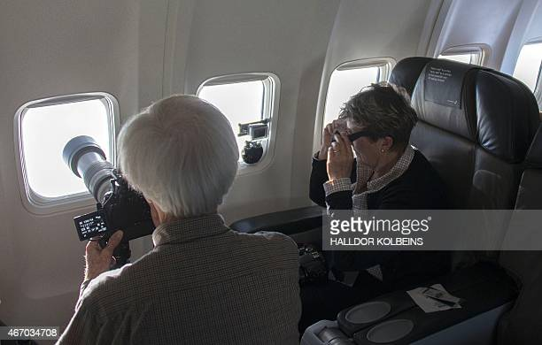 Passengers take photos of a partial solar eclipse on March 20, 2015 above the Faroe Islands from a Boeing 737 chartered by a science magazine. A...
