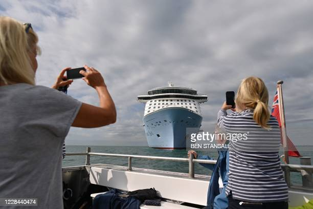 Passengers take pictures of the cruise ship 'Anthem of the Seas' during a Mudeford Ferry's cruise ship tour off the Dorset coast in southern England...