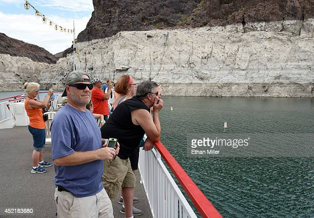 Passengers taking a boat tour including Michael Westman of Colorado pass in front of a mineralstained rock wall on July 14 2014 in the Lake Mead...