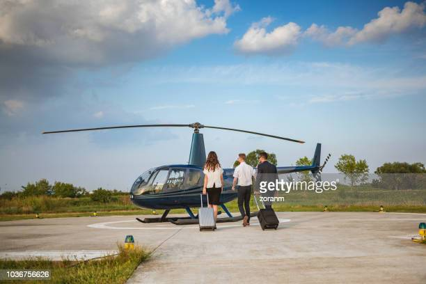 passengers taking luggage to helicopter - helicopter rotors stock photos and pictures