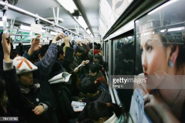 Passengers travel in a crowded subway train carriage on December 12 2007 in Beijing China Beijing is developing its subway system to boost the use of...