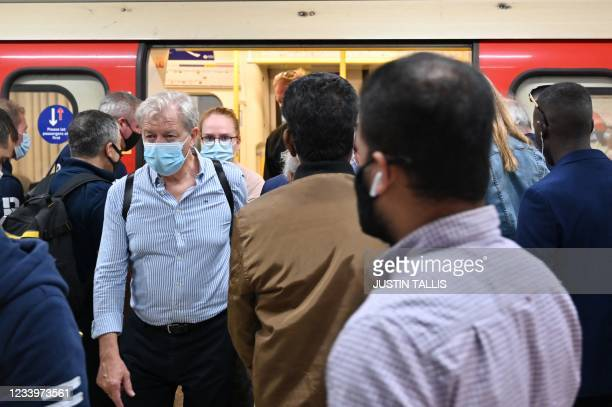 Passengers travel on the London Underground in central London on July 14, 2021. - London Mayor Sadiq Khan called for use of face coverings to remain...