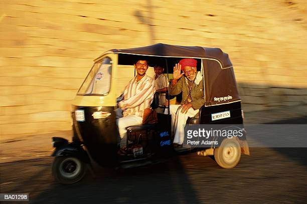 passengers traveling in auto rickshaw - auto rickshaw stock pictures, royalty-free photos & images