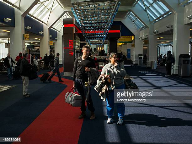 Passengers traveling on a US Airways flight look for their departure gate March 22, 2015 at LaGuardia Airport in the Queens borough of New York.