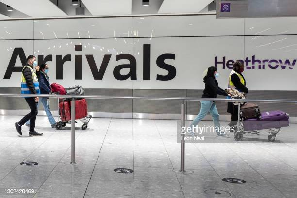 """Passengers travelling from one of the countries on the """"red list"""" are escorted through the arrivals area of terminal 5 of Heathrow airport and onto a..."""
