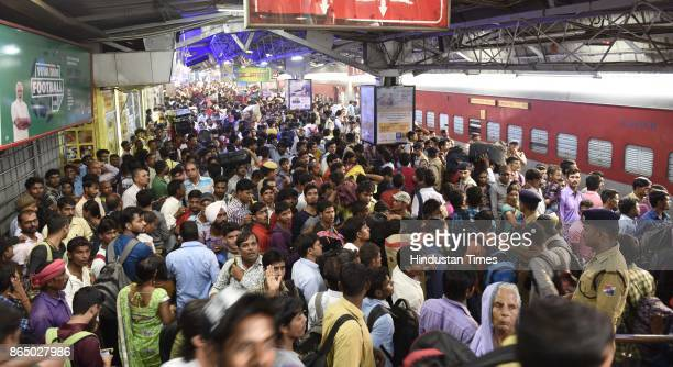 Passengers try to board the stationed 12394 Sampoorn Kranti Express train which runs from New Delhi to Patna to go to their native place for the...