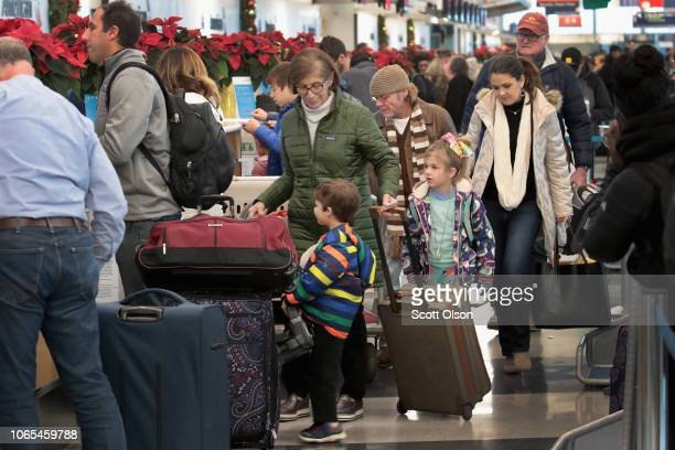 Passengers try to catch flights out of O'Hare International Airport after an early winter snowstorm caused the delay and cancellation of hundreds of...