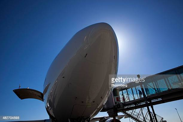 Passengers use a walkway to board an Airbus A330300 jet operated by Iberia airlines a unit of International Consolidated Airlines Group SA as it...
