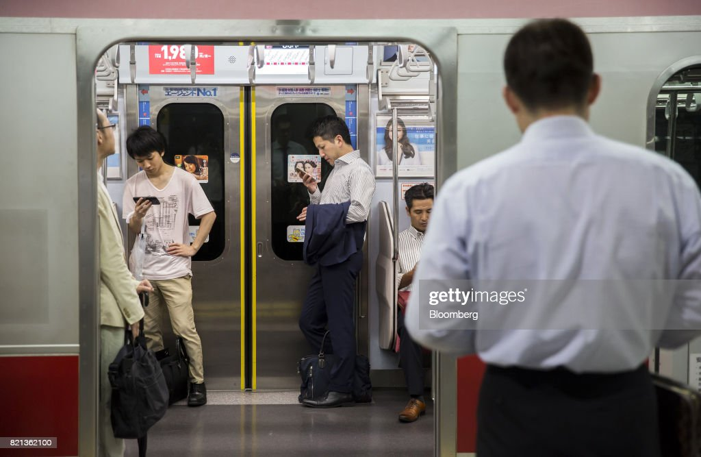 Passengers use smartphones wait while riding a train on the Toyoko line train operated by Tokyu Corp. at Shibuya Station in Tokyo, Japan, on Tuesday, July 18, 2017. July 24 marks the first dry run of a 'Telework Day' encouraging people to work from home as the city gears up to host the 2020 Summer Olympics. Authorities are seeking ways to make room for 920,000 spectatorsexpected to visit Tokyo each day during the games. Photographer: Tomohiro Ohsumi/Bloomberg via Getty Images