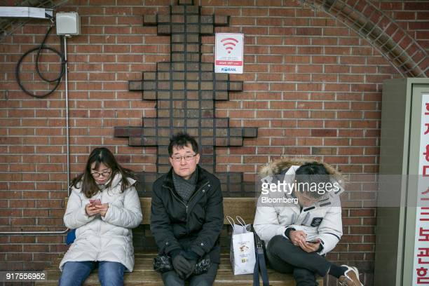 Passengers use smartphones while sitting under a a sign for the KT Corp Olleh Giga WiFi internet service inside a subway station in Seongnam South...