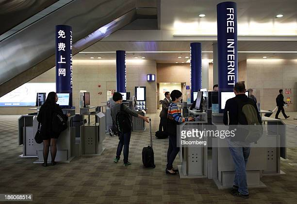 Passengers use the free Internet service at Shanghai Pudong International Airport in Shanghai China on Tuesday Oct 15 2013 Airline profits worldwide...