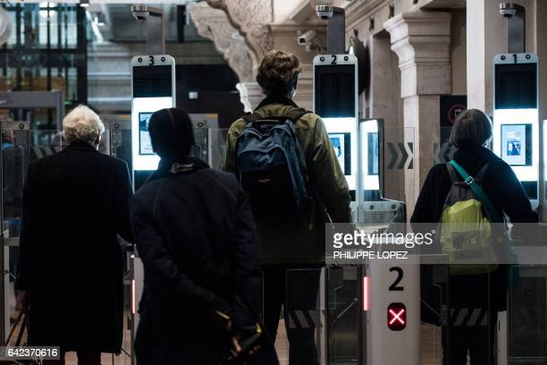 Passengers use their biometric passport at an automated ePassport gate equiped with a facial recognition system at the British border of the Eurostar...