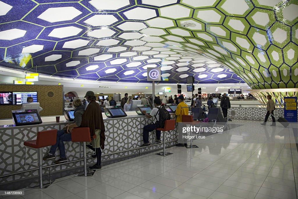 Passengers using internet terminals at Abu Dhabi International Airport. : Bildbanksbilder