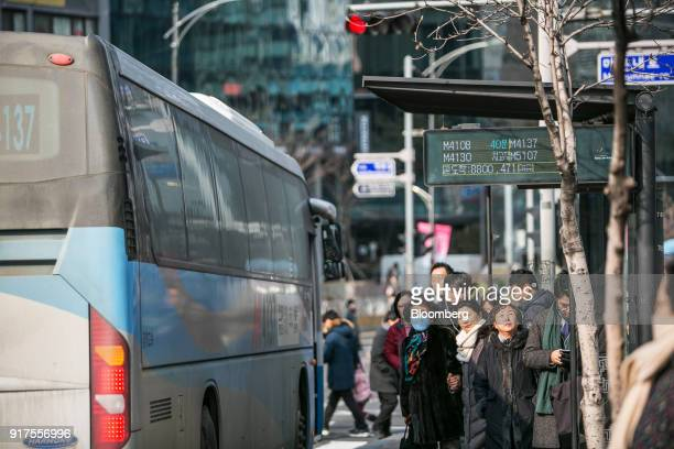 Passengers wait as a monitor displays the estimated arrival times of buses at a bus stop in Seoul South Korea on Sunday Jan 28 2018 5G the...