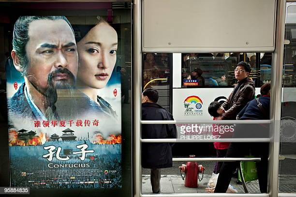 Passengers wait at a bus stop where a poster of forthcoming Chinese movie 'Confucius' is displayed in Shanghai on January 20 2010 China's Internet...