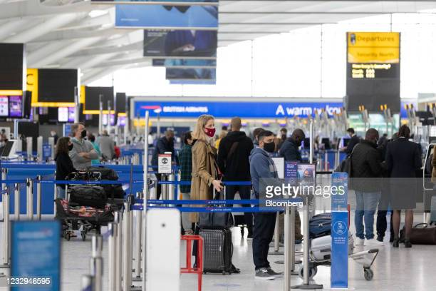 Passengers wait at check-in desks in the departures hall in Terminal 5 at London Heathrow Airport in London, U.K., on Monday, May 17, 2021. After a...