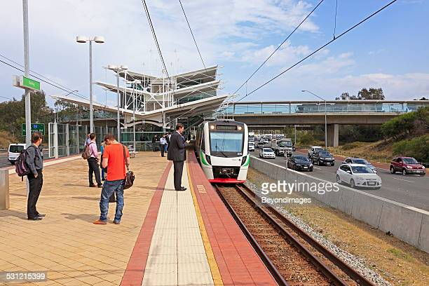 Passengers wait at station with train, bus, traffic on freeway