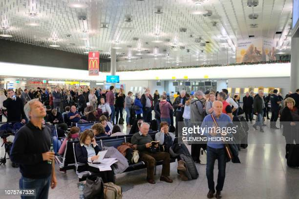 Passengers wait at the airport in Hanover on December 29 2018 after a security incident resulted in flight operations been suspended when a man broke...