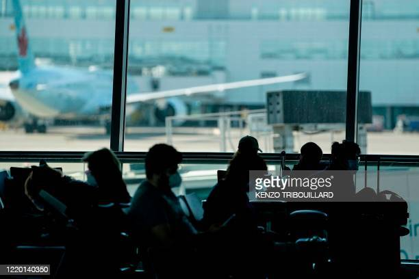 Passengers wait at the boarding gate at Brussels Airport, in Zaventem, on June 15, 2020 as Brussels Airport reopens for travels within Europe and the...