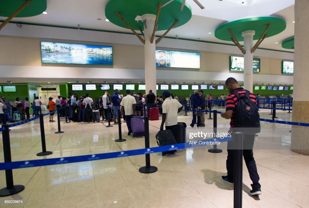 Passengers wait at the counters of the airport of Punta Cana, in the Dominican Republic, where flights have been suspended or cancelled as Hurricane Maria approaches on September 20, 2017. Hurricane Maria slammed into Puerto Rico on Wednesday, cutting power on most of the US territory as terrified residents hunkered down in the face of the island's worst storm in living memory. The US and British Virgin Islands -- still struggling to recover from the devastation of Irma -- are also on alert, along with the Turks and Caicos Islands and parts of the Dominican Republic. / AFP PHOTO / Erika SANTELICES
