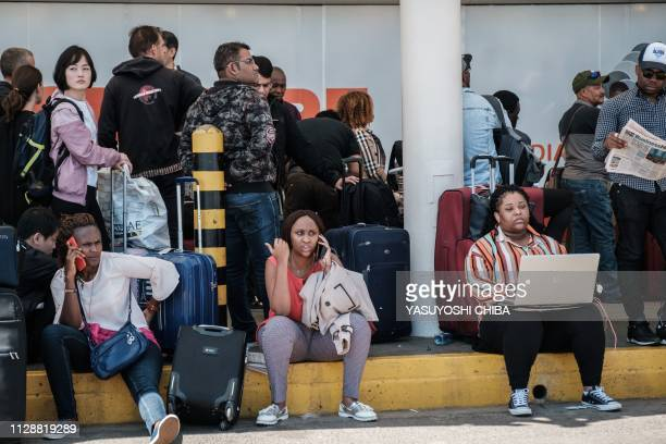 Passengers wait at the entrance of Kenya Airway's depature terminal during a strike by airline workers at the Jomo Kenyatta International Airport in...