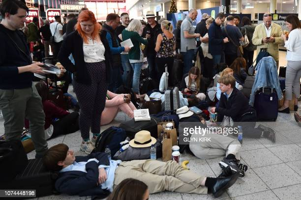 Passengers wait at the North Terminal at London Gatwick Airport south of London on December 20 2018 after all flights were grounded due to drones...