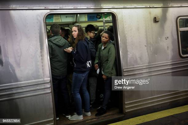 Passengers wait for a train to leave the station at the HoytSchermerhorn subway station April 12 2018 in the Brooklyn borough of New York City A...